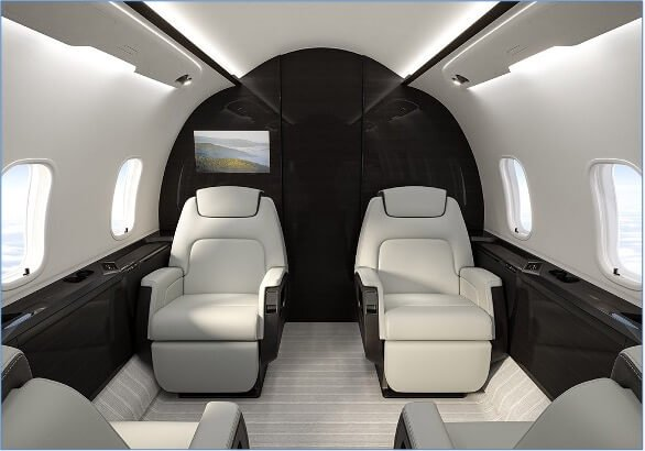 Challenger 350 main cabin, with four executive-style seats upholstered with white leather in club configuration, light grey striped carpeting, black wood paneling, white walls, and HD monitor display.